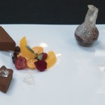 Citrus Bavarois, passion fruit skin, mango fluid gel, liquid chocolate with flame ice wine jelly, sparkling fruits, Saskatoon berry and rose soup (in blown sugar flask)